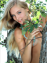 Blue eyed teen posing naked under a tree