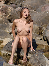 Pretty dark blonde takes her cloth off in the water and remains naked